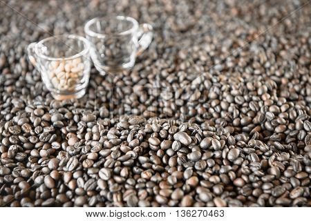 Roasted coffee beans with blurry 2 coffee cups on background.