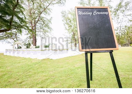 blank chalkboard sign with brown wooden frame in front of wedding ceremony. Wedding Decoration