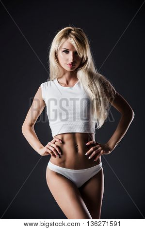 poster of Fitness blonde woman shows her body. Fitness motivation. Perfect female sports figure. Fitness woman posing in the studio. Fitness photo shoot in the studio. Fitness bikini.