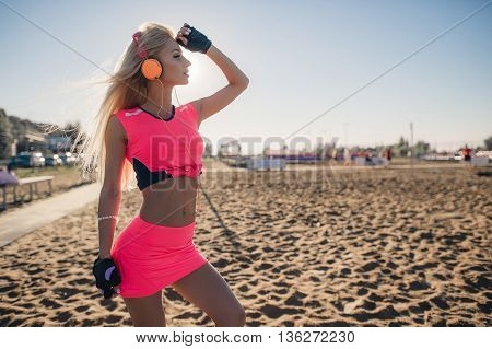 Fitness model athlete girl in colorful sportswear with headphones posing and listening music outdoors on beach or sports ground before workout at evening summer.