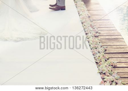 Sweetness white walkway on wodden bridge to wedding ceremony beautiful flowers on the side decorated with blurry background part of bride and groom. Copy space. Text space.