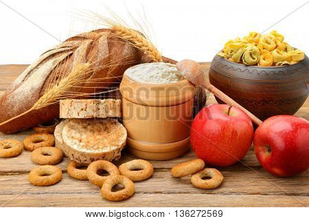 Products made of wheat on table isolated on white background