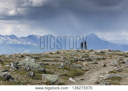 A pair of tourists watches an approaching storm from the top of a mountain - Jasper National Park Canada
