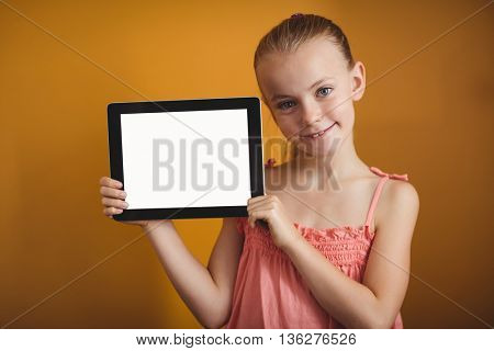 Girl holding a tablet on yellow background