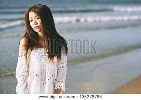 Portrait of beautiful Asian girl standing on serene beach