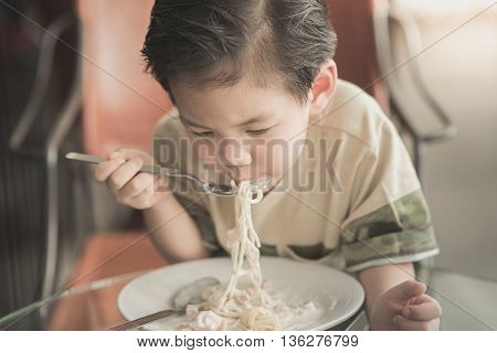 Cute Asian chid eating Spaghetti Carbonara in restaurant vintage fiter