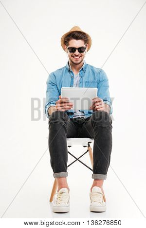 Handsome attractive smiling happy young male using tablet and sitting on the chair isolated on the white background