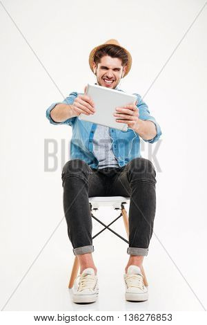 Portrait of a funny casual man playing using tablet computer isolated on a white background