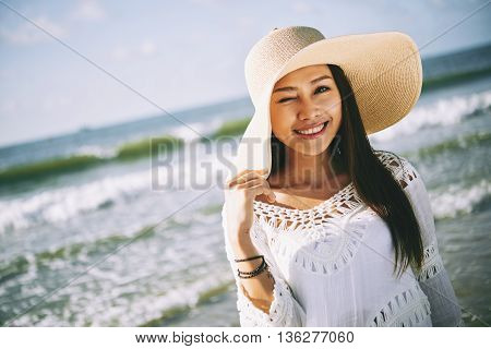 Lovely Vietnamese young lady enjoying sun at the beach