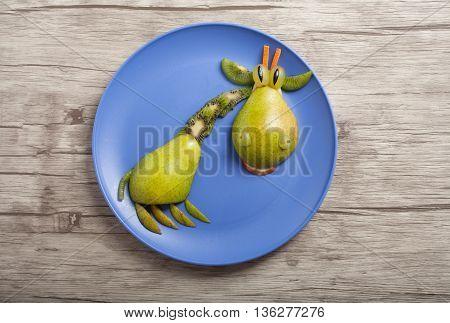 Giraffe made of pear and kiwi on plate