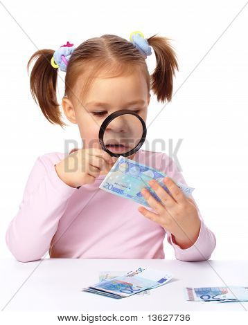 Girl Is Looking At Euro Banknote Using Magnifier