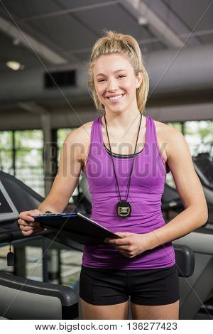 Portrait of gym instructor holding clipboard in gym