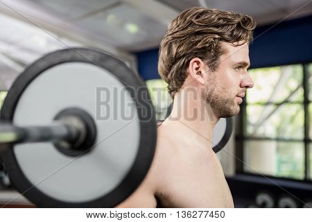 Man working out with barbell at gym