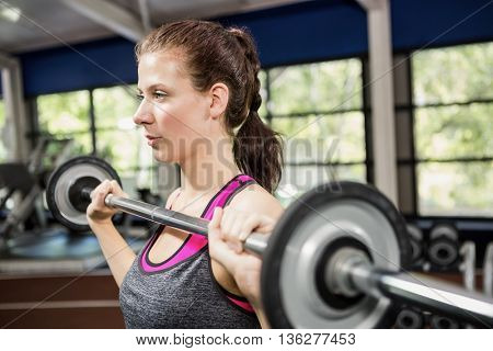 Close-up of woman working out with barbell at gym