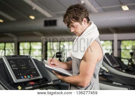 Gym instructor writing on clipboard in gym