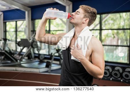 Man drinking water after workout at gym