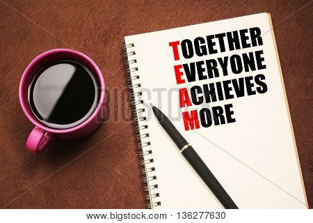 Team Acronym - text on notebook with a pen and cup of coffee