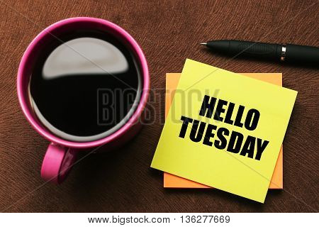 Hello Tuesday - text on sticky note with a pen and cup of coffee