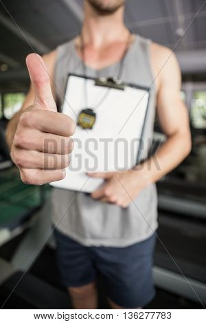 Close-up of trainer showing his thumbs up at gym