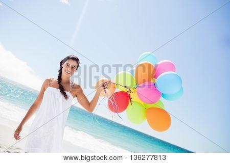 Beautiful woman holding balloon on the beach
