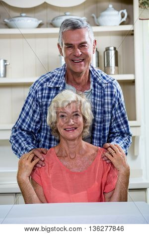 Portrait of smiling senior couple in kitchen at home
