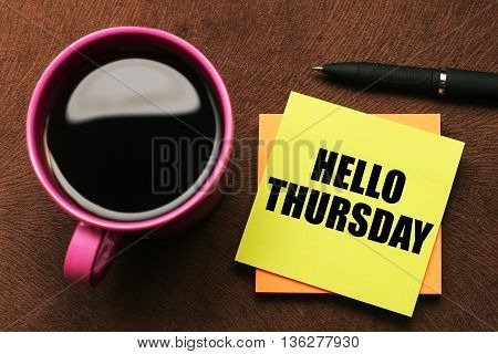 Hello Thursday - text on sticky note with a pen and cup of coffee