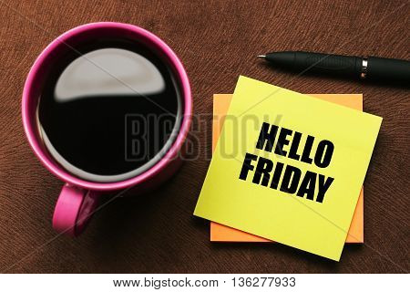 Hello Friday - text on sticky note with a pen and cup of coffee