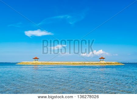 Indonesian style beach hut built on a man made island just off the coast on a sunny clear day.