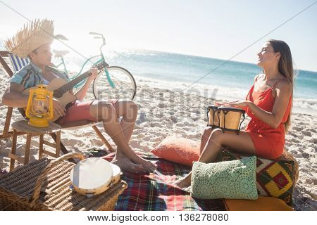 Friends lying and playing music together on the beach