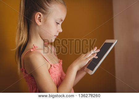 Little girl using a tablet on yellow background