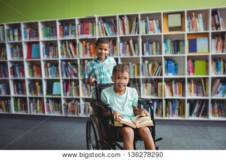 Little boys holding a book in the library