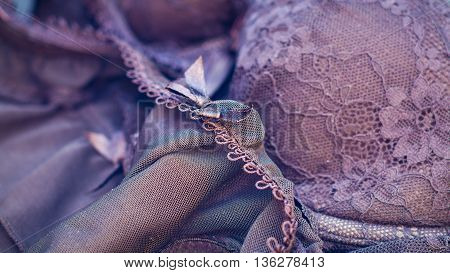 An abstract closeup of woman's lingerie with overall purple tone adding to the feel of romance and seduction.