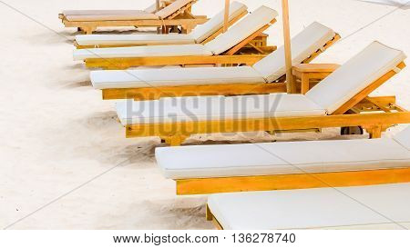 A row of sun lounger chairs on a white sandy beach with white umbrella. Bali - Indonesia