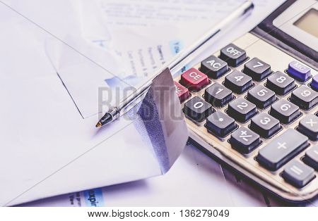 Bills a calculator and a pen. The cocept here is personal finances.