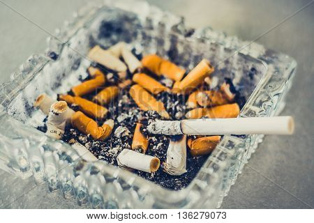 A cigarette burning in an glass ashtray thats full of butts.