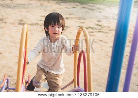 Happy asian child on slide at playground