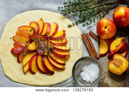 Baking a fruit pie with peaches nectarines. The ingredients on the table - dough peaches nectarines sugar cinnamon thyme. Selective focus