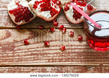Pomegranate seeds and pomegranate juice in glass on old wooden table. Selective focus