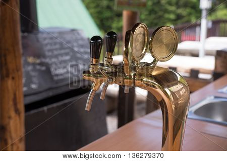Golden beer taps at the bar with blurry background