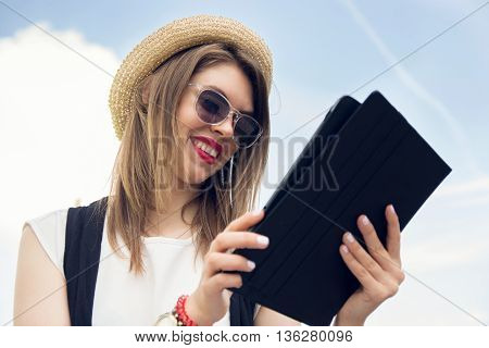 Young Woman In Sunglasses And Hat Sitting Park With Tablet