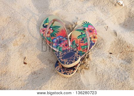 Colorful flipflop on the white sand beach summer day