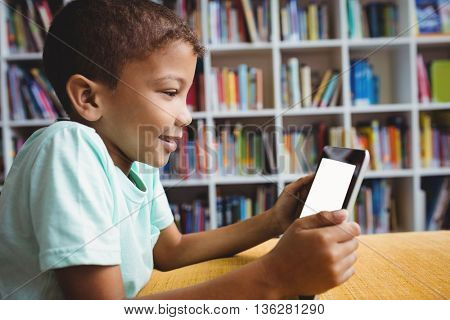Little boy using a tablet in the library
