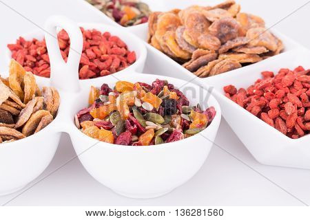 Dried fruits berries and seeds in bowls closeup picture.