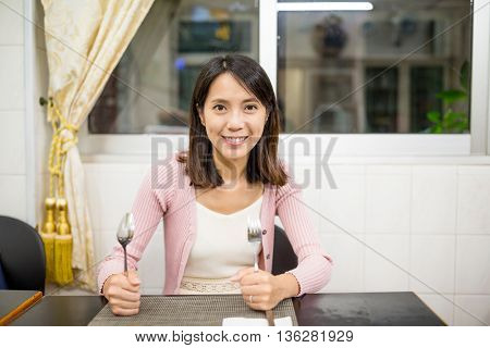 Woman holding knife and fork in restaurant