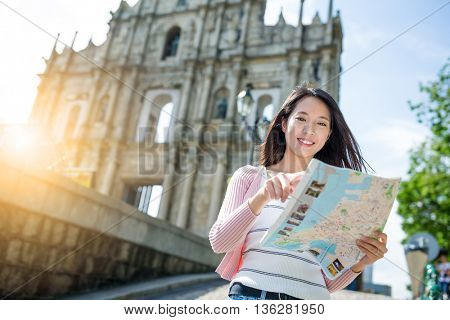 Woman use of paper map in macau city