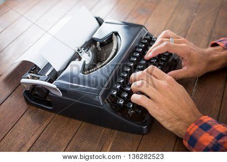 Hipster man using a typewriter at work