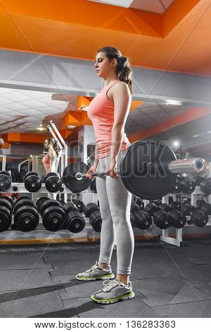Sportswoman lifting hard barbell at gym interior. Young pretty bodybuilder woman in sportsuit doing workout with bar at gym against the mirror wall