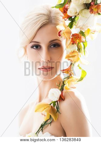 Portrait of gorgeous, young bride in white dress posing with flowers.