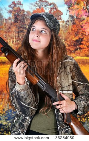 Closeup of a  pretty young teen hunter in camouflage near an autumn woods and wetlands.  She's looking up with a rifle in her hands.