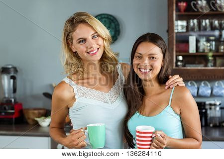 Portrait of happy female friends holding coffee cups in kitchen at home
